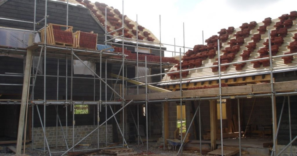House under construction showing larch cladding on left and roof being tiled on right