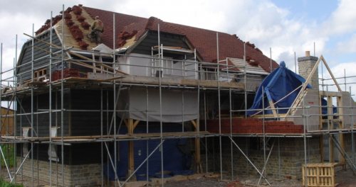 House under construction, larch cladding, man laying tiles