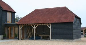 New garage with larch cladding and red tile roof