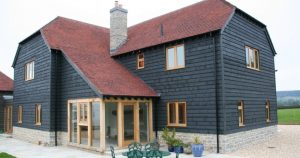 New house with larch cladding and red tile roof
