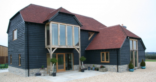New house with larch cladding and red tile roof. Picture windows at front