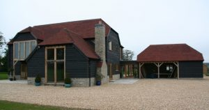 New house with larch cladding and red tile roof. Picture windows at front. Garage to the side
