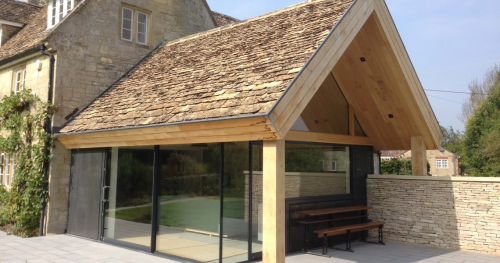 House extension with floor to ceiling windows, wooden roof with traditional tiles