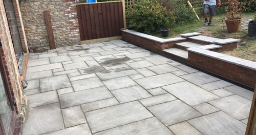 Porcelain patio with steps leading to lawn